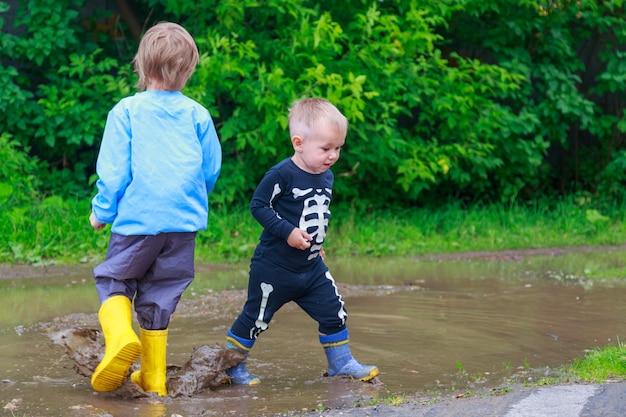 고무 장화와 비옷을 입은 아이들이 웅덩이에서 놀다