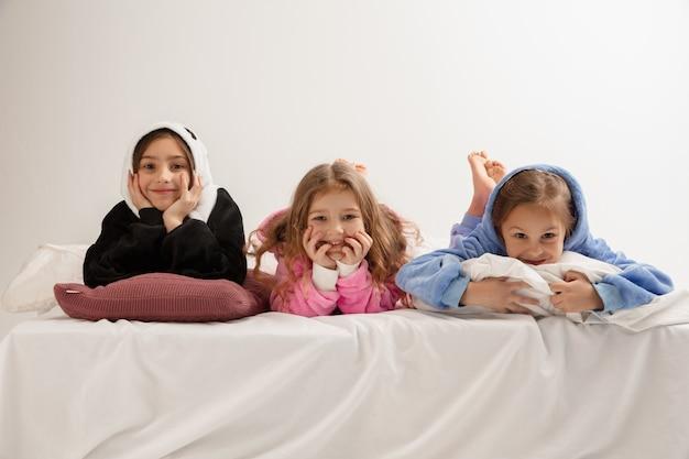 柔らかく暖かいパジャマを着た子供たちは、家で遊んでいる明るい色をしていました。楽しんで、パーティーをして、笑って、一緒に遊んでいる小さな女の子は、スタイリッシュで幸せそうに見えます。子供の頃、レジャー活動、幸福の概念。