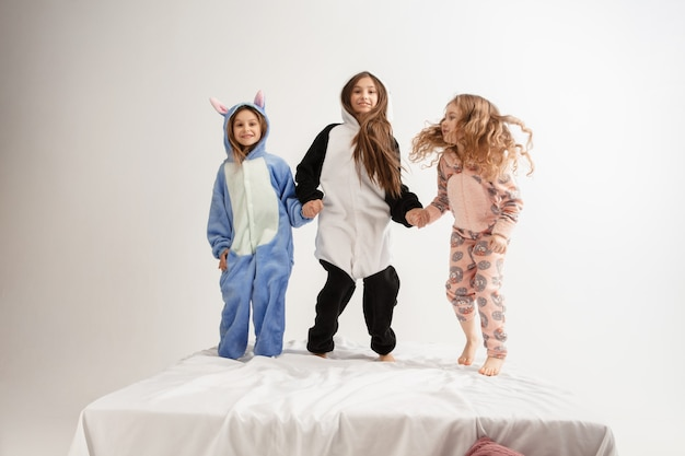 家で遊んで明るい色のパーティーをしている柔らかく暖かいパジャマの子供たち
