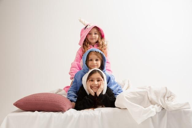 부드럽고 따뜻한 잠옷을 입은 아이들이 집에서 밝은 색으로 놀고 있는 파티를 하고 있다