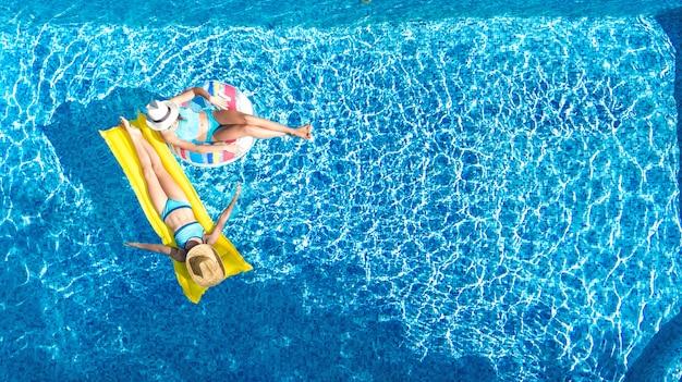 위의 수영장 공중 무인 항공기보기 어린이, 행복한 아이들이 풍선 링 도넛과 매트리스에서 수영, 적극적인 소녀는 휴가 리조트에서 가족 휴가에 물에서 재미를