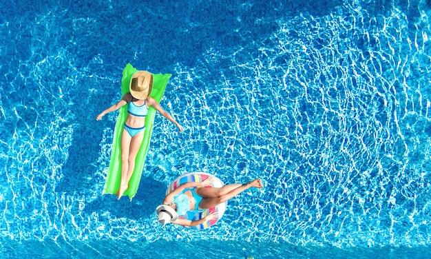 Дети в бассейне с высоты птичьего полета, вид сверху счастливые дети плавают на надувном кольцевом пончике