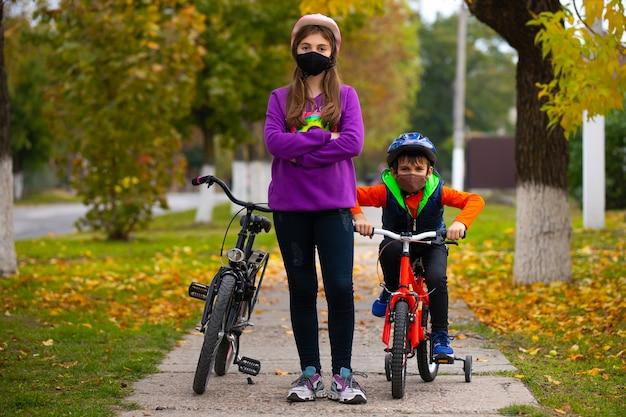 Дети в осеннем парке катаются на велосипедах в защитных масках. расплывчатый осенний парк в стене. фотография с пустым боковым пространством. концепция пандемии и вируса.
