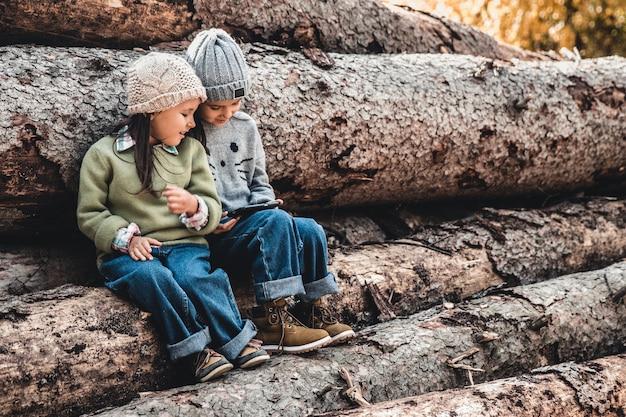 Дети на фоне бревен играют со смартфоном. смотрите видео и получайте удовольствие. дружба, сестры, семья.