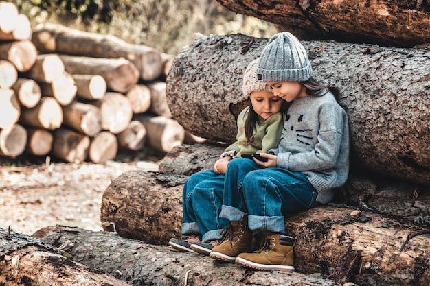 Дети на фоне бревен играют со смартфоном.