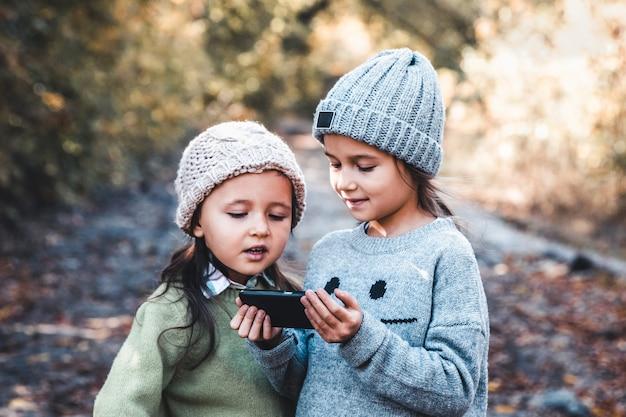 자연의 배경에있는 아이들은 스마트 폰으로 놀아요. 비디오를보고 재미있게 보내십시오. 우정