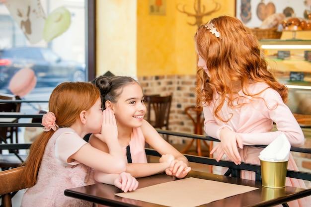 テーブルのカフェの子供たちは注文するお菓子を選びます
