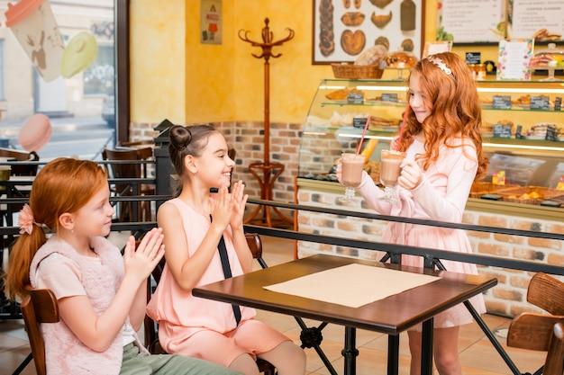 カフェの子供たちはテーブルに座って喜ぶ