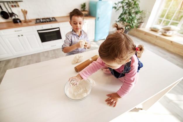 台所の子供たちは小麦粉で遊んでいます。