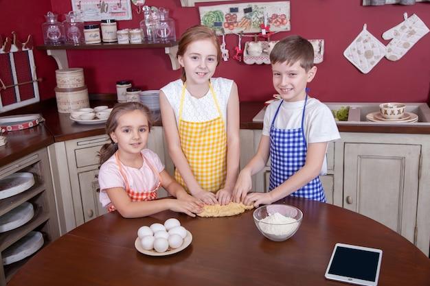 料理を学ぼうとしている台所の子供たち。エプロンの親友がペストリーを手に持ち、キッチンでケーキを作り、お互いを見つめています。スタジオショット。