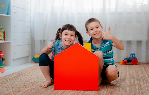 赤いおもちゃの家のある保育園の子供たち