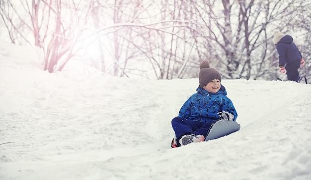 겨울에 공원에 있는 아이들. 아이들은 놀이터에서 눈을 가지고 놀고 있습니다. 그들은 눈사람을 조각하고 언덕을 미끄러져 내려갑니다.