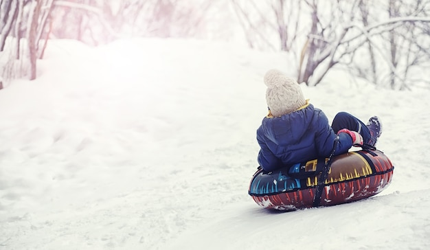 冬の公園の子供たち。子供たちは遊び場で雪で遊ぶ。彼らは雪だるまを彫刻し、丘を滑り降ります。