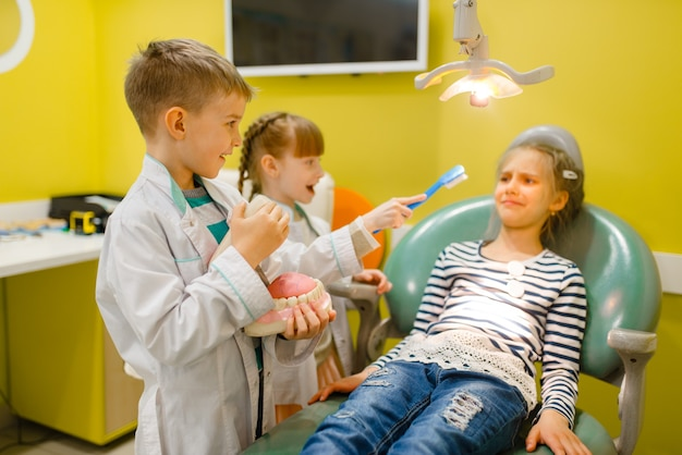 Дети в униформе, играя врача стоматолога