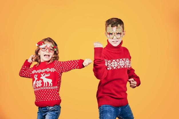 Дети в теплых красных рождественских свитерах Premium Фотографии
