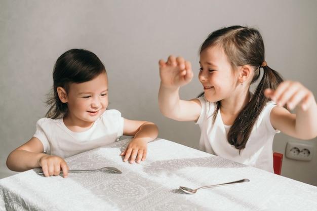 아이들은 테이블에 탐닉합니다. 음식을 기다리는 두 자매