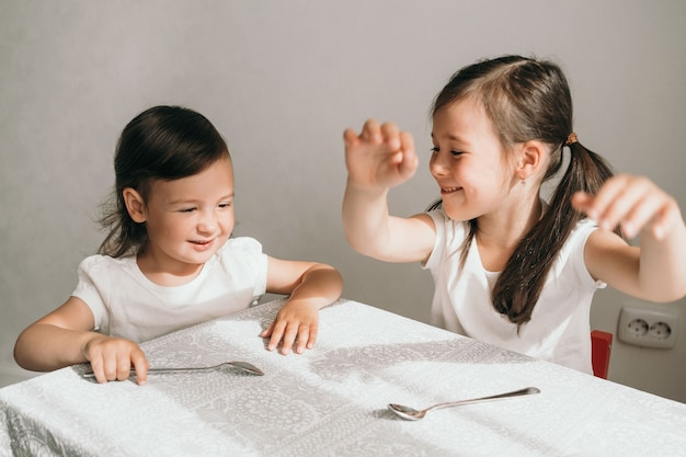 Children indulge at the table. two sisters are waiting for food