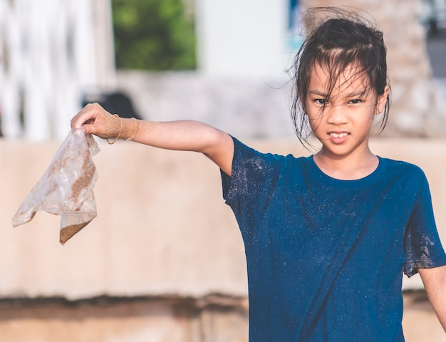 Children is holding plastic bag that he found on the beach
