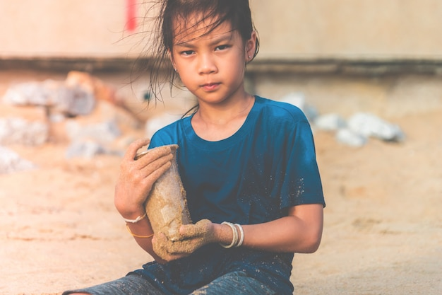 Children is holding plastic bottle that he found on the beach