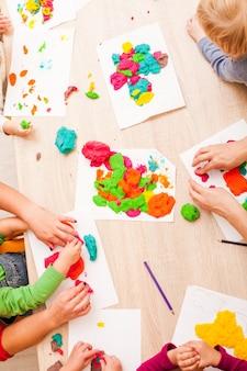 아이들이 탁자에서 모형 찰흙을 가지고 놀고 있다