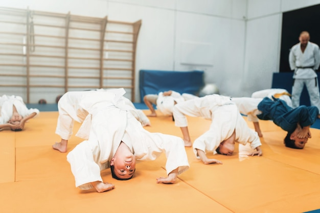 子供柔道、着物の子供たちは体育館で武道を練習します。スポーツトレーニングで制服を着た小さな男の子と女の子