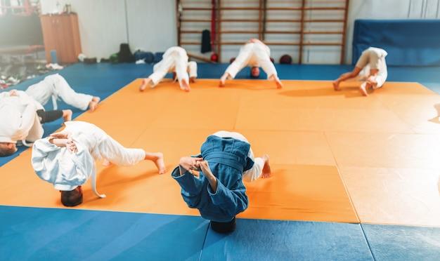 子供の柔道、着物姿の子供たちがホールで武道を練習。スポーツトレーニングの制服を着た男の子と女の子