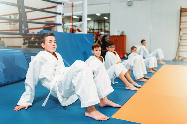 Children judo, kids in kimono practice martial art in hall. little boys and girls in uniform on sport training