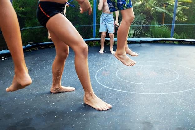 수영 트렁크를 들고 트램폴린에서 점프하고 그룹에서 친구들을 즐기는 아이들