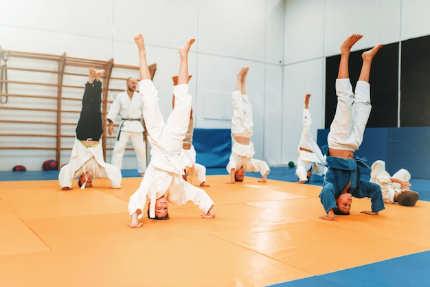 Children karate, kids practice martial art in hall