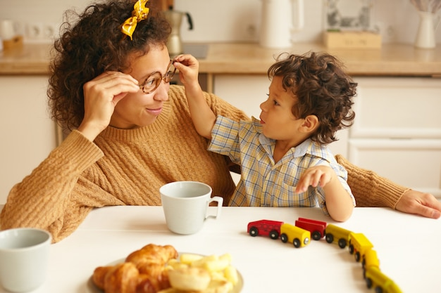 Children, kids, happy childhood, family bonds and parenting concept. picture of attractive young hispanic woman having coffee at ktichen table and smiling while infant son taking off her eyeglasses