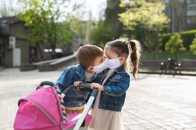 子供たちは防護マスクでキスします。コロナウイルス、covid-19