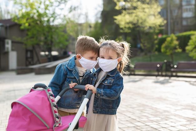 어린이들은 보호용 안면 마스크를 쓰고 키스합니다. 코로나 바이러스 (코로나 19