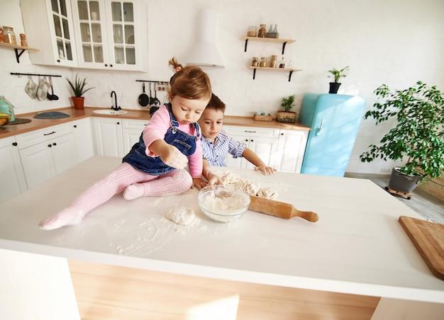子供たちは台所のテーブルで生地をこねます