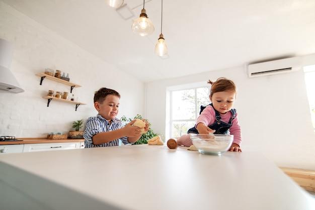 子供たちは台所のテーブルに座って生地をこねます