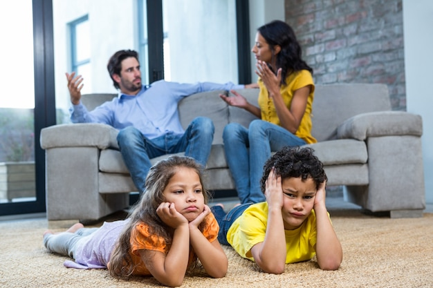 Children laying on the carpet in living room