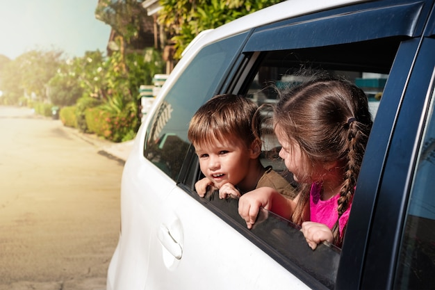 Дети высовываются из окна машины и смотрят на улицу