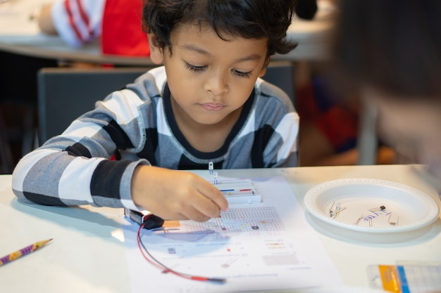Children learn to connect electric circuits in the classroom.