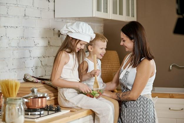 子供たちは台所でサラダを準備する方法を学びます。家族の休日、自分の手で昼食。ママと若い料理人