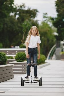 子供たちは晴れた夏の日に公園でホバーボードに乗ることを学ぶ
