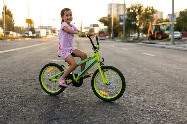 Children learning to drivebicycle on a driveway outside. little girls riding bikes on asphalt road in the city wearing helmets as protective gear.