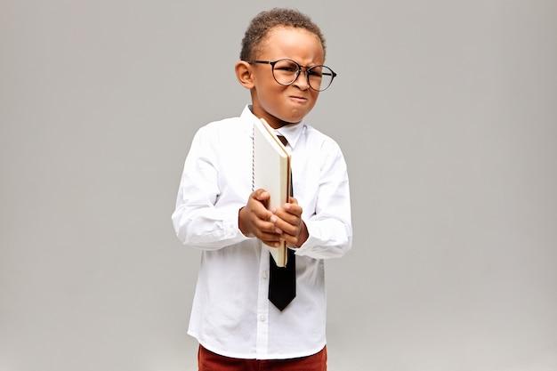 子供、学習、教育、知識の概念。白いシャツ、ネクタイ、眼鏡をかけ、コピーブックを持って顔をゆがめ、数学を怠ったために怒っている怒っている小さなアフリカの少年の肖像画