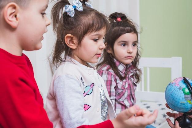 Bambini che imparano il globo in camera da letto