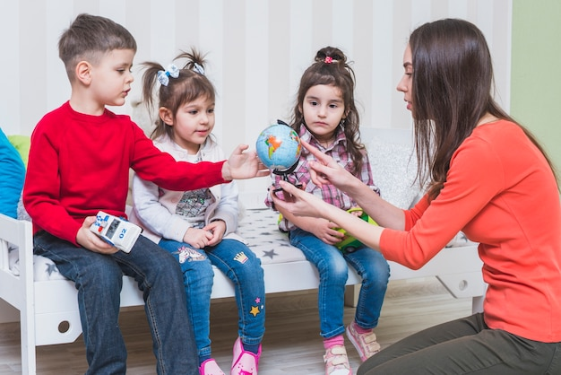Children learning globe with woman in bedroom