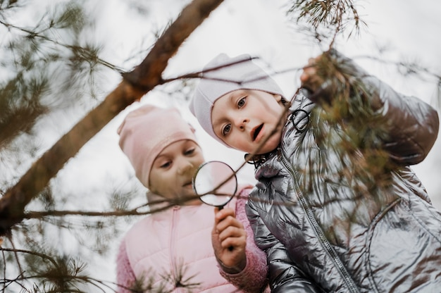 Children learning science in the nature with a magnifier