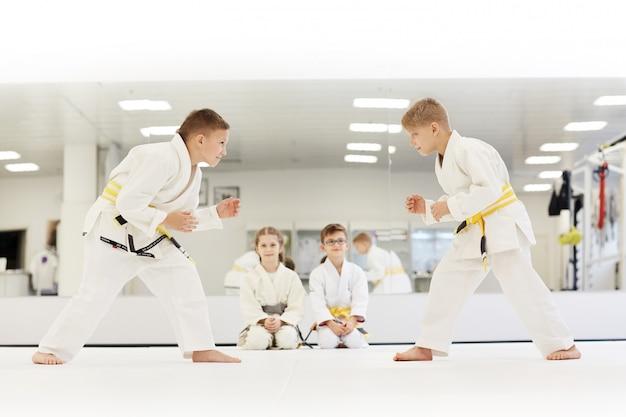 Дети учатся сражаться на уроке каратэ