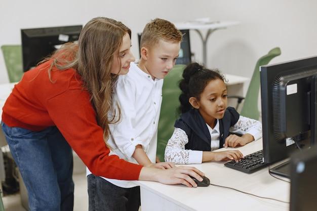 아이들은 컴퓨터에서 일하는 법을 배웁니다. 테이블에 앉아 아프리카 소녀입니다. 컴퓨터 과학 수업에서 소년과 소녀.