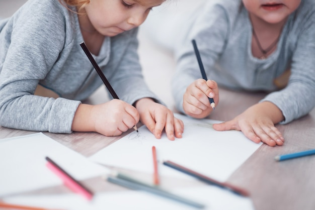 Children lie on the floor in pajamas and draw with pencils. cute child painting by pencils. hand of child girl and boy draw and paint with crayon. close up view.