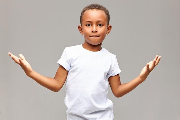 Bambini, stile di vita e linguaggio del corpo. colpo isolato del ragazzino afroamericano bello bello che ha sguardo fiducioso che morde il labbro inferiore e che fa il gesto con i palmi, mostrando che non ha paura