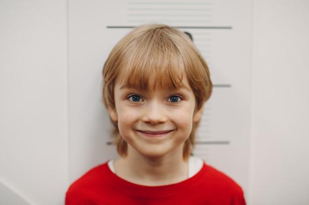 Детский маленький мальчик измеряется ростом роста на настенных весах портрет улыбки ребенка