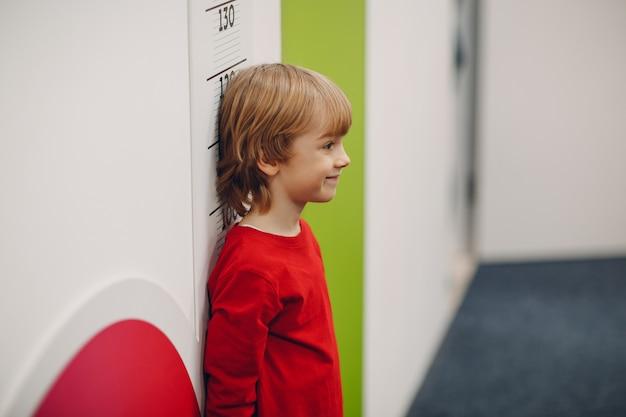 子供の小さな男の子は壁のスケールで成長の高さを測定されます